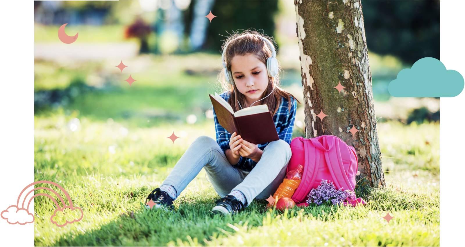 Enfant qui lit un livre en dessous d'un arbre dans un parc